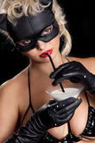 Black cat drinking milk. Portrait of the blonde model wearing black cat, licking - drinking milk from the martini glass royalty free stock images