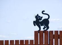 The black cat on a fence. The figure of a black cat on a fence Stock Photography