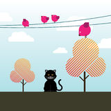 Black cat, magenta birds and Fall trees. A Black cat sitting face forward on a partly cloudy Fall day with magenta birds sitting on wires and trees above it Stock Image