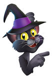 Black cat in witch hat. An illustration of a black witches cat in pointy witch hat leaning round a Halloween sign or banner and pointing Royalty Free Stock Photos