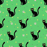Black cats seamless pattern. Sitting black cat on a green background with paw print vector illustration