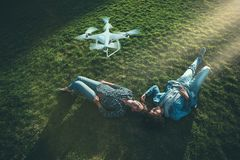 Black and Caucasian girl on the grass, flying UAV above stock photo