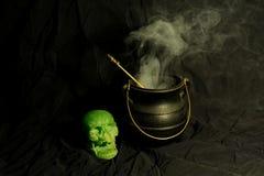 Black cauldron with skull and smoke. Old black cauldron with smoke and green skull on black background Stock Photos