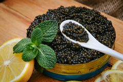 Black caviar in a bowl on the table royalty free stock photography