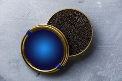 Black caviar in can. Black Sturgeon caviar in can on concrete background royalty free stock photo