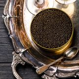 Black caviar in can and champagne on silver tray. On black wooden background close-up stock photo