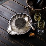 Black caviar in can on ice in silver bowl and champagne. On black wooden background stock photos