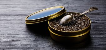 Black caviar in can and spoon. On black wooden background copy space stock images