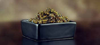 Black Caviar closeup. Natural sturgeon black caviar in square dish on black background. Delicatessen stock images