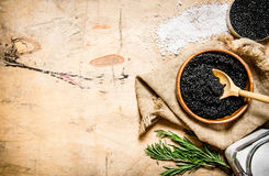 Black caviar. The concept of black caviar. Black caviar in a cup with salt and rosemary. On a wooden table. Free space for text . Top view royalty free stock photography