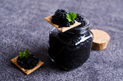 Black caviar on a cracker. On a dark background. Selective focus royalty free stock images