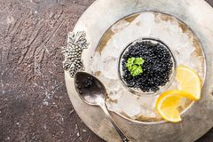 Black caviar on ice. Black caviar in a glass bowl on ice with lemon close up over dark background, top view stock photo