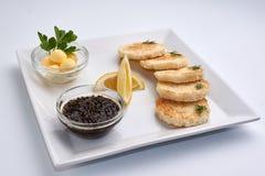 Black caviar. Lemon. Greens. Bread and butter Stock Photos