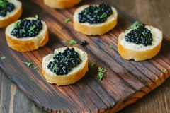 Black caviar on the pieces of bread over wooden kitchen board. Black caviar on the pieces of bread over wooden kitchen board Stock Photos