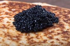 Black caviar on Russian pancakes - blini royalty free stock photography