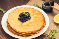 Black caviar on Russian pancakes - blini. Selective focus. Wooden background. Top view. Close-up stock photography