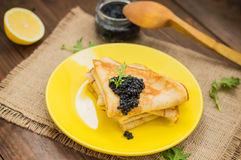 Black caviar on Russian pancakes - blini. Selective focus. Black caviar on Russian pancakes - blini on a yellow plate. Selective focus. Wooden background. Top royalty free stock images