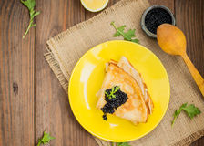 Black caviar on Russian pancakes - blini. Selective focus. Black caviar on Russian pancakes - blini on a yellow plate. Selective focus. Wooden background. Top royalty free stock photo