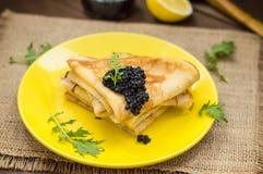 Black caviar on Russian pancakes - blini. Selective focus. Stock Photos