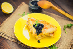 Black caviar on Russian pancakes - blini. Selective focus. Black caviar on Russian pancakes - blini on a yellow plate. Selective focus. Wooden background. Top stock photo
