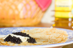 Black caviar on Russian pancakes. Selective focus. royalty free stock images