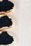 Black caviar on a slice of bread and butter Stock Photos