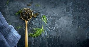 Black caviar in a spoon on dark background. Natural sturgeon black caviar closeup. Delicatessen. Top view. Flatlay royalty free stock photos