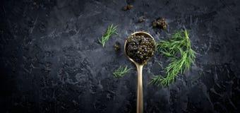 Black caviar in a spoon on dark background. Natural sturgeon black caviar closeup. Delicatessen. Top view, flatlay royalty free stock image
