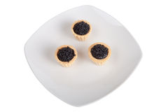 Black caviar in tartlets on white plate, isolated on white backg Royalty Free Stock Image