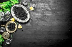 Black caviar with vodka and lemon slices. On a black chalkboard Royalty Free Stock Images