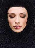 Black caviar and woman. Face of young beauty woman in black caviar Royalty Free Stock Images