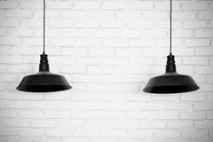 Black ceiling lamps . Two black ceiling lamps, light betwe stock photos