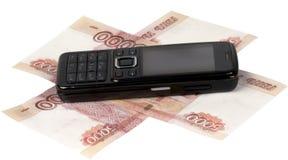 Black cellular telephone on money Stock Photos