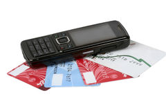 Black cellular telephone on plastic cards Stock Photos