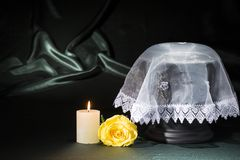 Black cemetery urn with burning candle, white lace shroud, yellow rose on deep green background. For obituary card Royalty Free Stock Photography