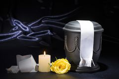 Black cemetery urn with burning candle and white ribbon yellow rose on deep blue background. For sympathy card Royalty Free Stock Photos