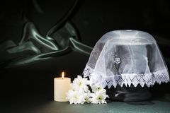 Black cemetery urn with burning candle white white lace shroud white chrysanthemum on deep green background. For sympathy card Stock Photography