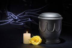 Black cemetery urn with burning candle yellow rose on deep blue background. For sympathy card Stock Images