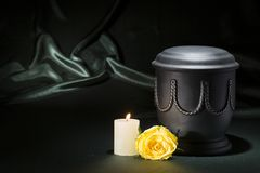 Black cemetery urn with churning candle yellow rose on dark green background. For obituary card Stock Photo