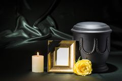 Black cemetery urn with golden mourning frame burning candle and yellow rose on dark green background. For sympathy card Stock Photos