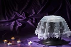 Black cemetery urn with white shroud candles on deep purple background. For mourning card Royalty Free Stock Images