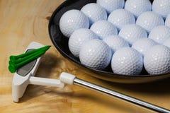 Black ceramic bowl full of golf balls and putter Royalty Free Stock Image