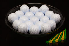 Black ceramic bowl full of golf balls Royalty Free Stock Image
