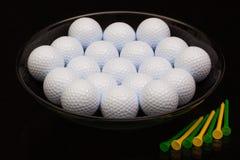 Black ceramic bowl full of golf balls. And tees Royalty Free Stock Image