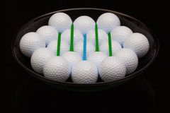 Black ceramic bowl full of golf balls Stock Images