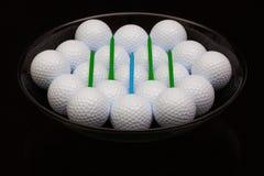 Black ceramic bowl full of golf balls. And tees Stock Images