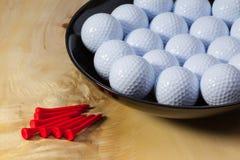 Black ceramic bowl full of white golf balls Stock Photos
