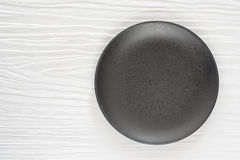 Black ceramic bowl on the white wooden. Table Royalty Free Stock Images