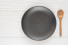 Black ceramic bowl and wooden spoon on the white wooden. Table Stock Photo