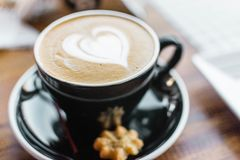 Black Ceramic Cup With Brown Liquid With Heart-shape on Black Ceramic Saucer Stock Image